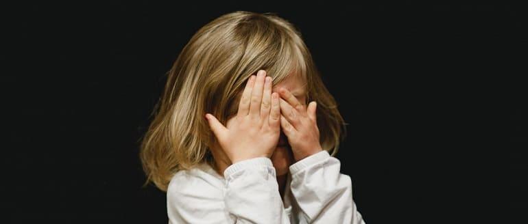 Ребенок закрывает лицо руками