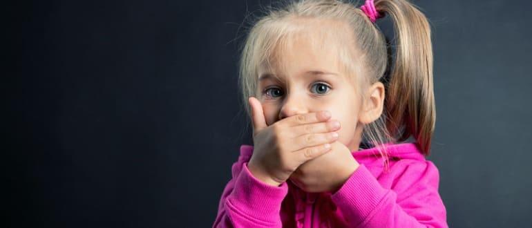 Девочка прикрывает рот рукой