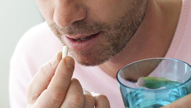 Парень пьет таблетку