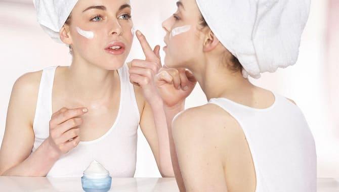 Девушка пользуется кремом для лица