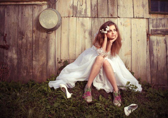 Девушка в свадебном платье сидит у сарая