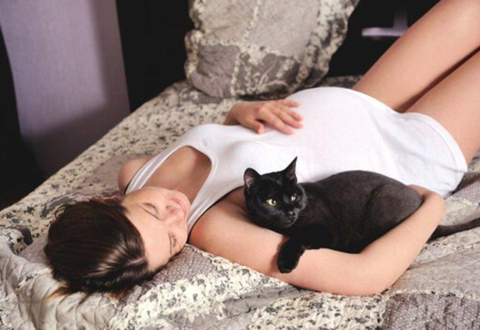 Беременная девушка и черный кот
