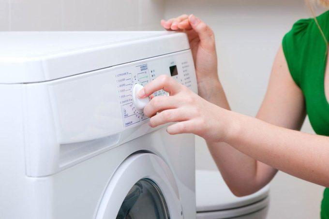 Девушка включает стиральную машину