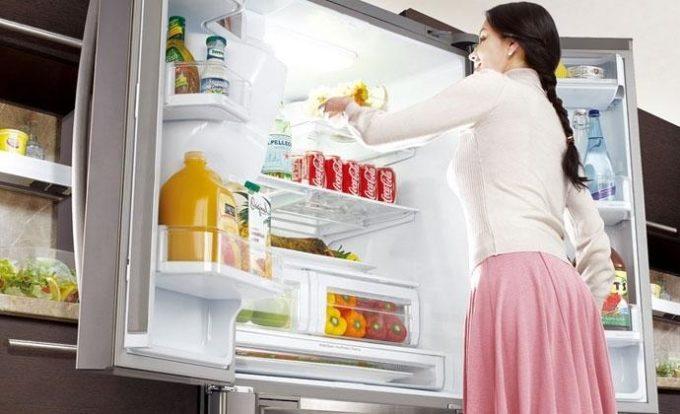 Девушка берет продукты из холодильника