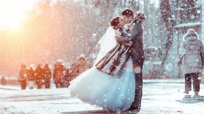 Молодожены целуются и идет снег