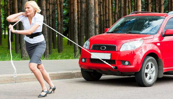 Девушка тянет машину на веревке