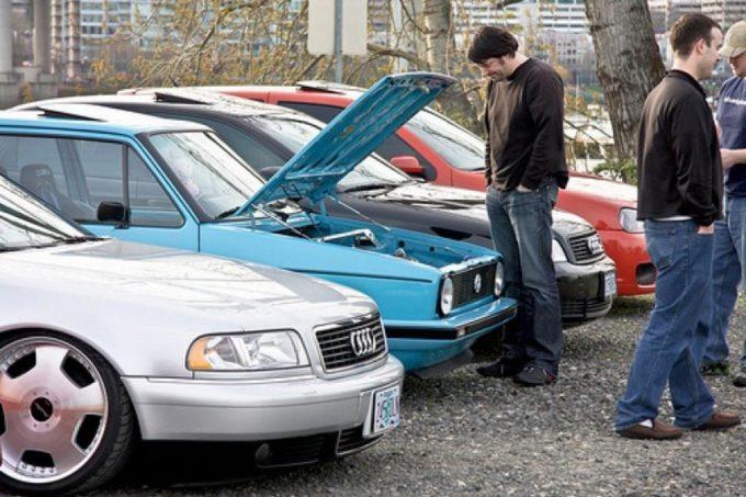 Парень смотрит под капот автомобиля