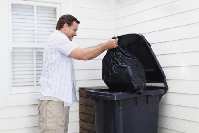 Мужчина выбрасывает мусор