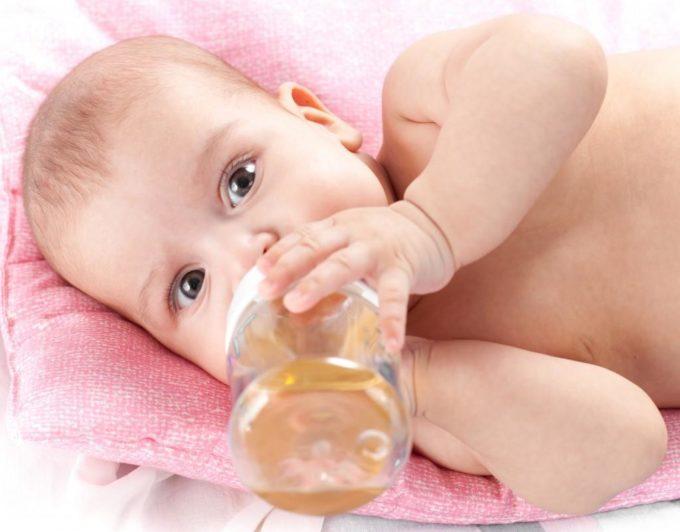 Ребенок пьет из бутылочки