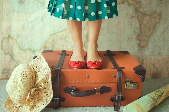 Девушка стоит на чемодане
